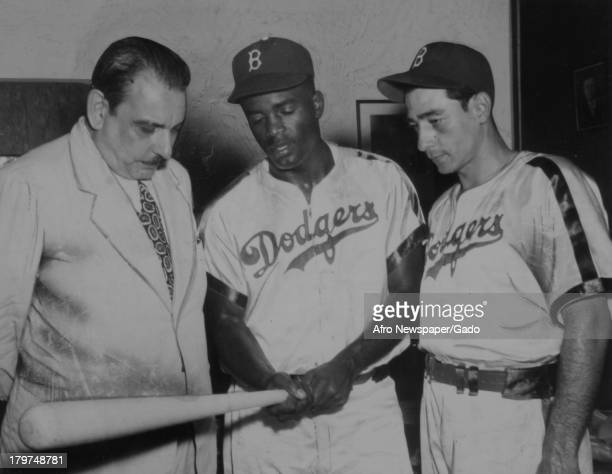 American baseball player Jackie Robinson of the Brooklyn Dodgers autographs bat for Governor Luis Muniz Marin of Puerto Rico at Ebbets Field New York...