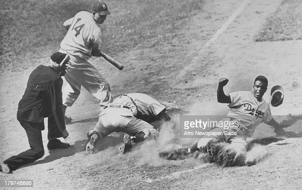 American baseball player Jackie Robinson of the Brooklyn Dodgers in action sliding past the other players towards home plate during a baseball game,...