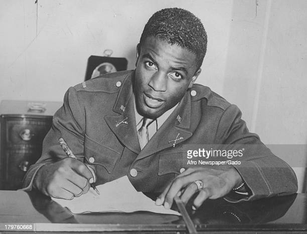 American baseball player Jackie Robinson of the Brooklyn Dodgers is signing paperwork January 3 1945