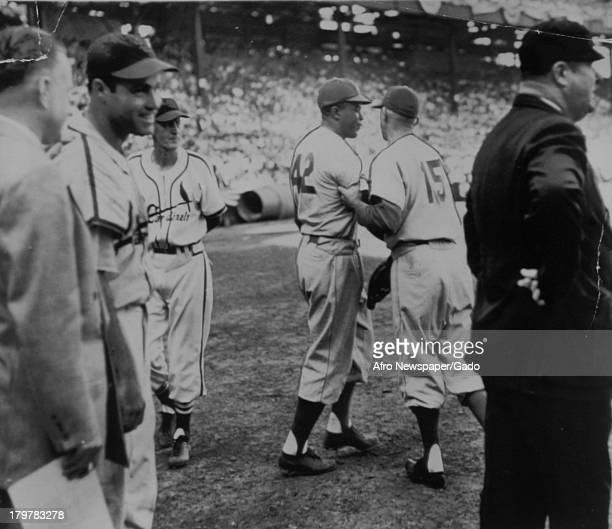 American baseball player Jackie Robinson of the Brooklyn Dodgers is restrained by coach Clyde during the verbal tiff in ninth inning of first game...
