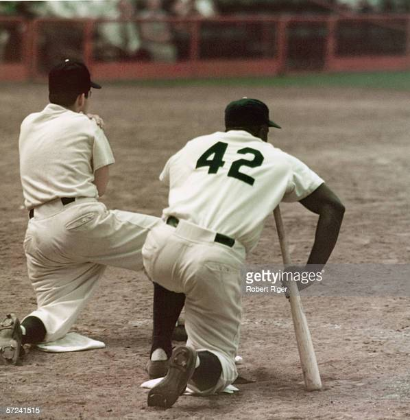 American baseball player Jackie Robinson of the Brooklyn Dodgers kneels on deck next to an unidentifed man 1950s