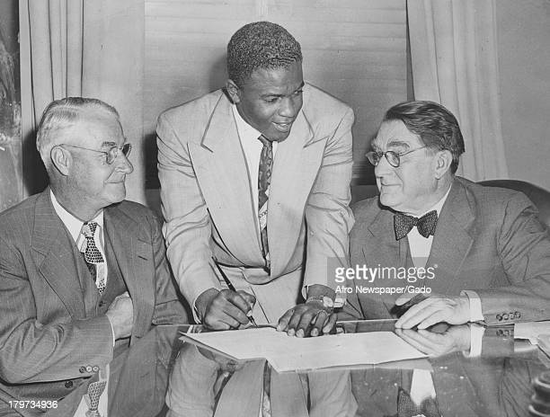 American baseball player Jackie Robinson of the Brooklyn Dodgers signs deal, 1947.