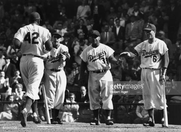 American baseball player Jackie Robinson of the Brooklyn Dodgers runs towards home plate to score as his teammates including Roy Campanella and Carl...