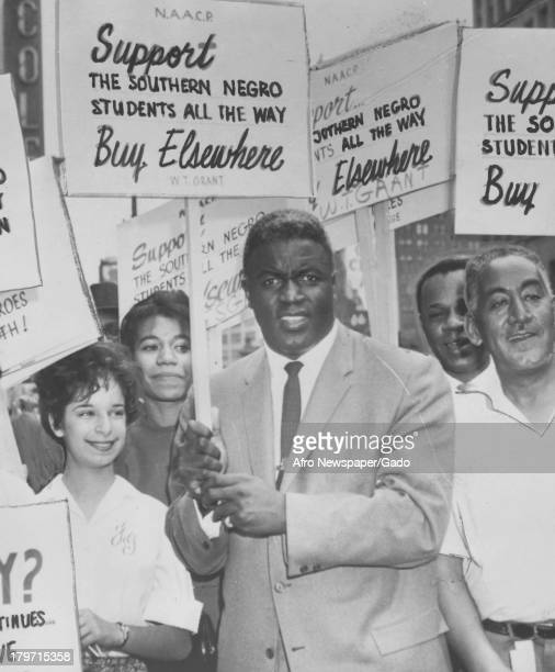 American baseball player Jackie Robinson of the Brooklyn Dodgers holds the National Association for the Advancement of Colored People placard in...