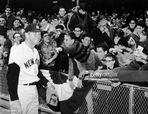 American baseball player Mickey Mantle of the New York Yankees smiles as young fans reach out to him on opening day at Tiger Stadium Detroit Michigan...