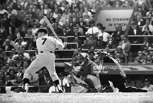 American baseball player Mickey Mantle of the New York Yankees continues to swing at bat in spite of leg pain during the World Series against the...