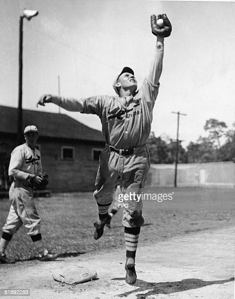 American baseball player Pepper Martin third baseman of the St Louis Cardinals leaps as he catches a ball in his glove during practice 1930s
