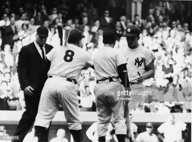 American baseball player Roger Maris of the New York Yankees is congratulated at home plate by Yogi Berra and the bat boy after hitting his record...
