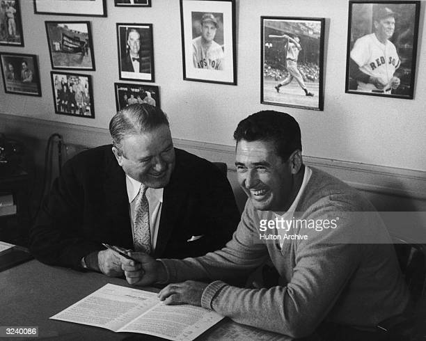 American baseball player Ted Williams smiles while signing a contract for Joe Cronin , manager of the Boston Red Sox.