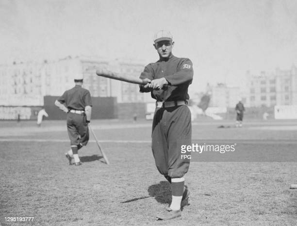 American baseball player Ty Cobb , Detroit Tigers outfielder, poses as if he is swinging a baseball bat, possibly on the training field, location...
