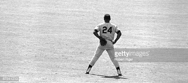 American baseball player Willie Mays stands in the outfield his gloved hand behind his back 1960s