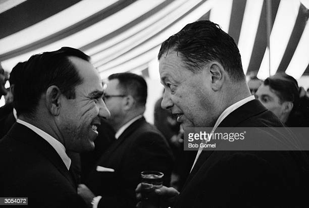 American baseball player Yogi Berra talks with restauranteur Bernard Toots Shor as the pair stand under a striped tent at the groundbreaking ceremony...
