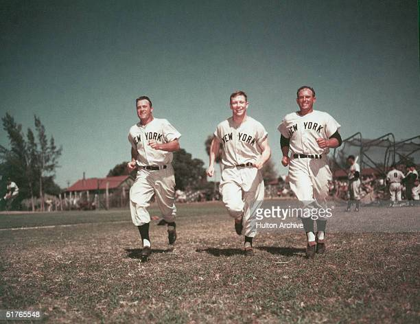 American baseball players from left Hank Bauer Mickey Mantle and Gene Woodling all outfielders in the uniform of the New York Yankees run together...