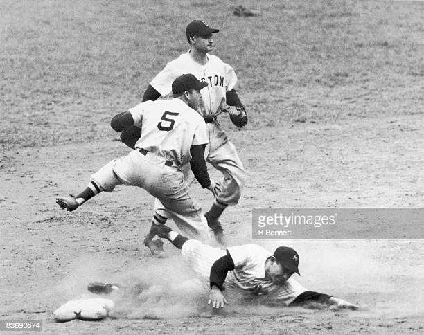 American baseball players Vern Stephens and Bobby Doerr of the Boston Red Sox watch a ball thrown by Stephens as Yogi Berra of the New York Yankees...
