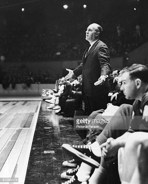 American basketball coach and sports executive Red Auerbach dressed in a suit and tie stands on the sidelines with his hands outstretched as he...