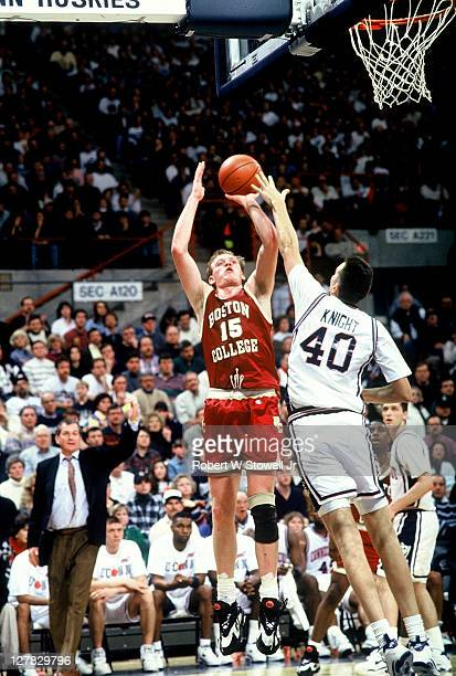 American basketball player Bill Curley of Boston College shoots over defense from Travis Knight of the University of Connecticut Storrs Connecticut...