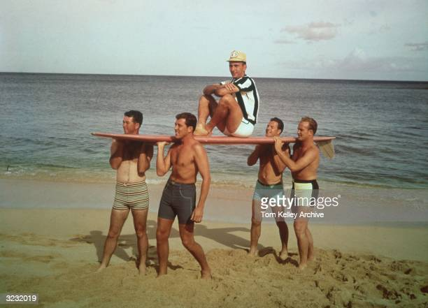 American basketball player Bob Cousy sitting on top of a surfboard carried by four fellow sportsmen in swimming trunks at the beach circa 1965 The...