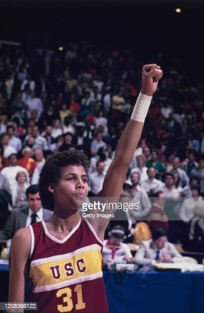 American basketball player Cheryl Miller of USC Trojans gives a clenched fist salute during an away game, circa 1983.