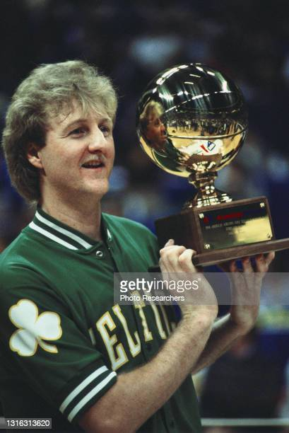 American basketball player Larry Bird, of the Boston Celtics, holds up his trophy, after winning the 1986 Three Point Contest at Reunion Arena,...