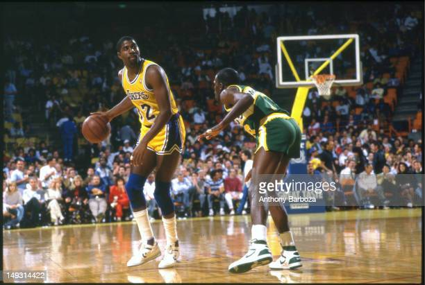 American basketball player Magic Johnson of the Los Angeles Lakers dribbles the ball as he looks up court his path blocked by Nate McMillian of the...
