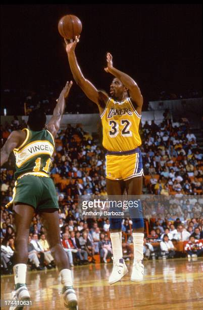 American basketball player Magic Johnson of the Los Angeles Lakers shoots the ball over the outstretched arm of Sam Vincent of the Seattle...