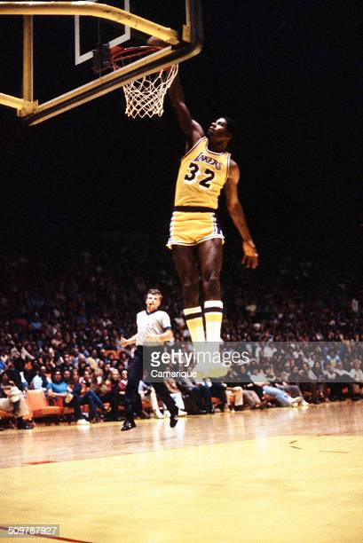American basketball player Magic Johnson of the Los Angeles Lakers dunks the ball during a game September 1982