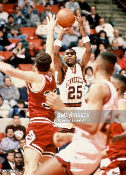 American basketball player Phil Gamble of the University of Connecticut shoots over Indiana University's defense Hartford Connecticut 1988