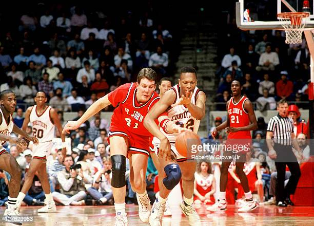 American basketball player Robert Werdann of St. John's University tries to steal the ball from Rod Sellers of the University of Connecticut during a...