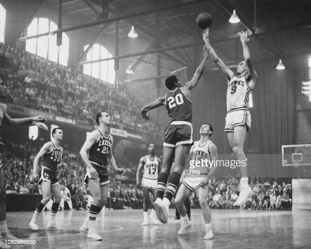 American basketball player Tom Hawkins , #20 for Los Angeles Lakers, attempts to block American basketball player Bob Pettit, #9 for St Louis Hawks ,...