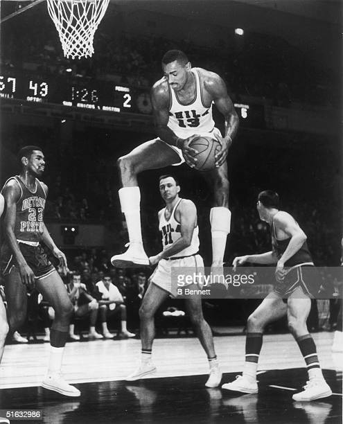 American basketball player Wilt Chamberlain in the uniform of the Philadelphia Warriors grabs a rebound in a game against the Detroit Pistons at...
