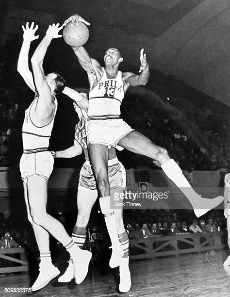 American basketball player Wilt Chamberlain of the Philadelphia Warriors grabs the ball during a game against the New York Knicks 1959