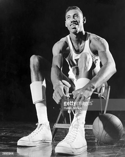 American basketball player Wilt Chamberlain wearing a University of Kansas uniform sits in a chair and ties his shoelace A basketball rests on the...