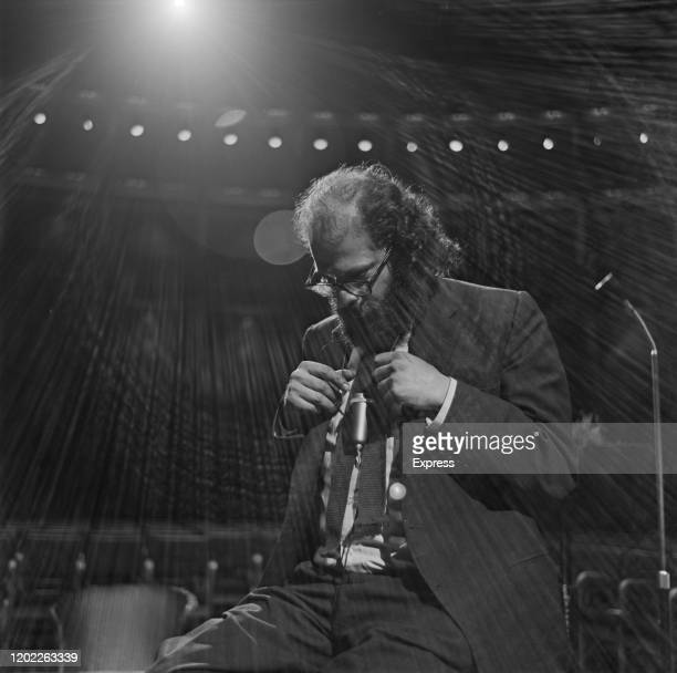 American beat poet Allen Ginsberg seated on stage during a rehearsal prior to appearing at the International Poetry Incarnation at the Royal Albert...