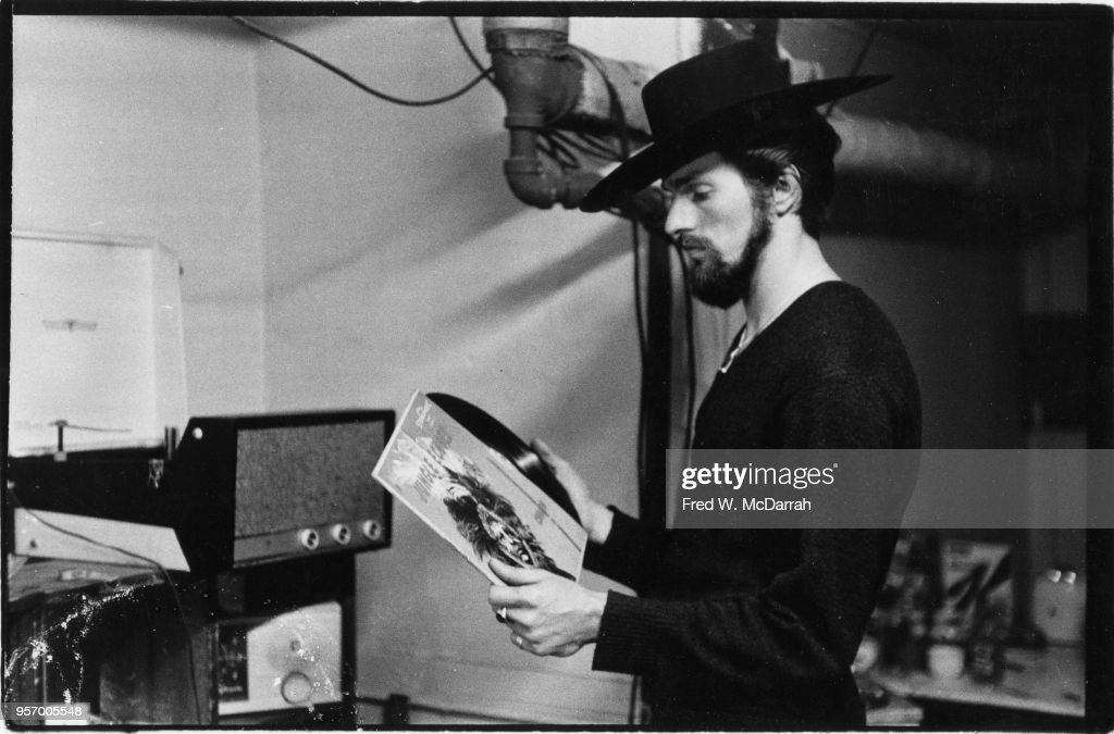 American beat poet and manager of Cafe Rafio Ronald Von Ehmsen (1932 - 1963) removes a record from its sleeve as he stands in his basement apartment (on St Mark's Place), New York, May 12, 1960.