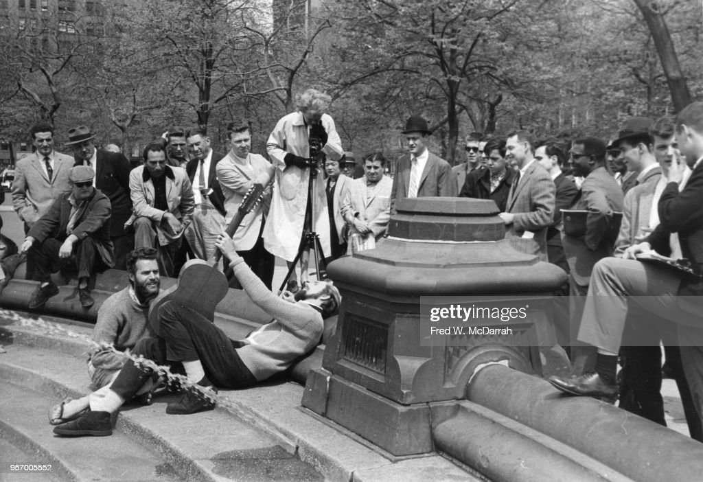 American beat poet and manager of Cafe Rafio Ronald Von Ehmsen (1932 - 1963) (center) lies back on the steps of the Washington Square Park fountain and plays guitar for an audience as an unidentified photographer takes his picture, New York, New York, April 28, 1960.