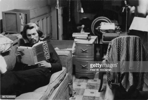 American beat poet and manager of Cafe Rafio Ronald Von Ehmsen reads a book as he sits on sits on a couch in his basement apartment New York May 12...