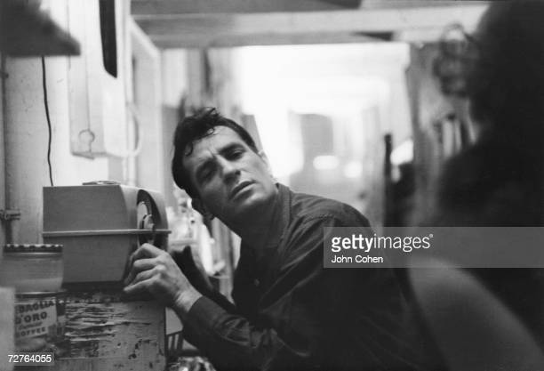 American Beat writer Jack Kerouac leans closer to a radio to hear himself on a broadcast 1959