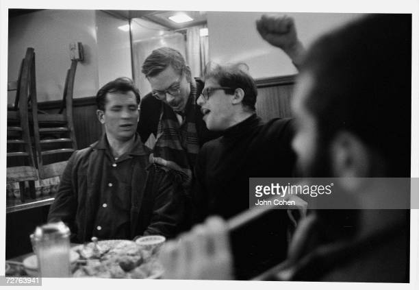 American Beat writers Jack Kerouac Lucien Carr and Allen Ginsberg enthusiastically sing a song together in an unidentified restaurant New York New...
