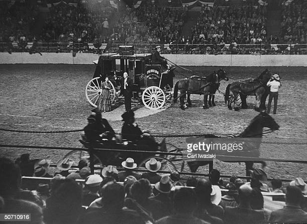 American Beauty Judy Johnston and Pres of Natl Western Stock show L M Pexton standing outside of stage coach waving to the crowd