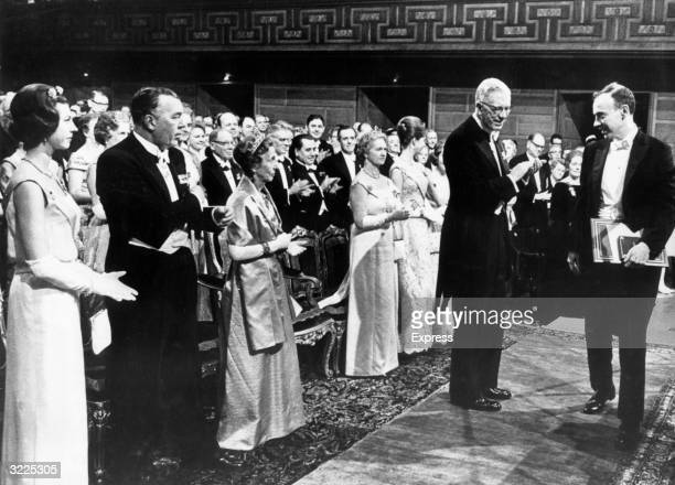 American biochemist James Dewey Watson receiving the Nobel Prize for Chemistry before a standing applauding crowd dressed in formal attire Stockholm...