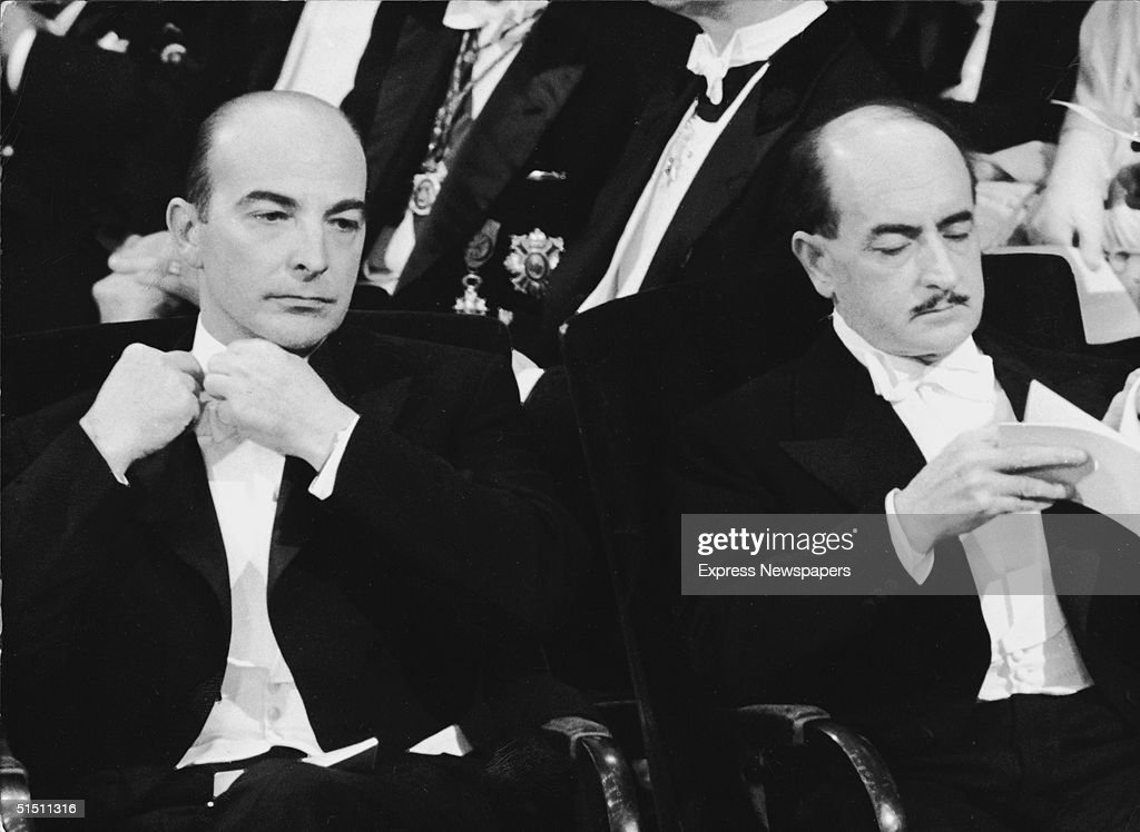 American biologist Arthur Kornberg (left), winner of the Nobel Prize for Medicine for his work (with Severo Ochoa) on RNA, sits with Italian Salvatore Quasimodo (1901 - 1968), winner of the Nobel Prize for Literature, as the pair await the arrival of the King & Queen of Sweden for the awards presentation ceremony, Stockholm, Sweden, December 14, 1959.