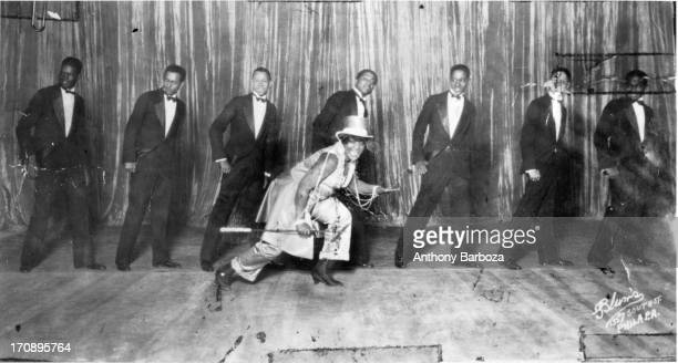American blues and jazz vocalist Bessie Smith dances on stage in front of a line of men, Philadelphia, Pennsylvania, early twentieth century.