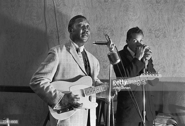 American blues guitarist songwriter and singer Muddy Waters and colleague harmonica player Isaac Washington pose for a photo while playing their...