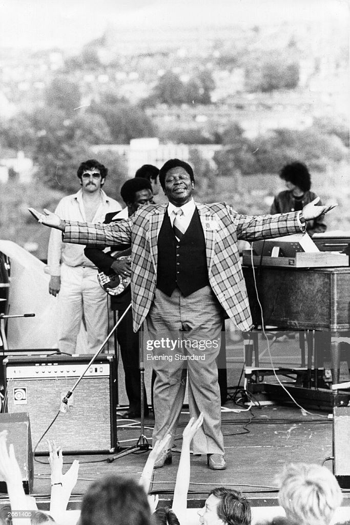 American blues musician B B King being the showman on stage at an outdoor concert.