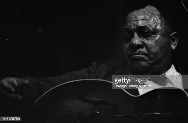 American Blues musician Big Joe Williams plays guitar as he performs onstage at the Folklife Festival Chicago Illinois 1961