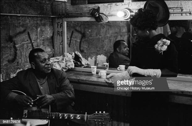 American Blues musician Big Joe Williams talks with Mary Ross backstage at the fourth annual University of Chicago Folk Festival Chicago Illinois...