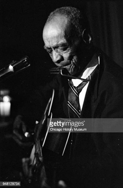 American Blues musician Daddy Stovepipe plays guitar and harmonica as he performs onstage at the Fickle Pickle nightclub Chicago Illinois June 1963