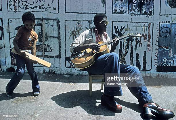 American blues musician Henry Saint Clair Fredericks best known for his stage name Taj Mahal playing the guitar in the street Berkeley CA 1974