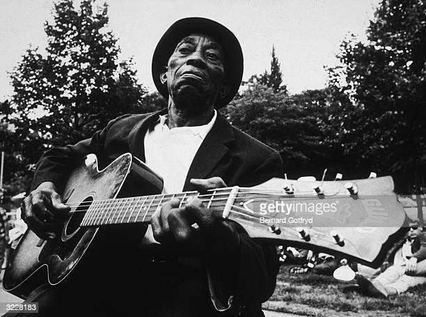 American blues musician Mississippi John Hurt plays guitar in Washington Square Park New York City