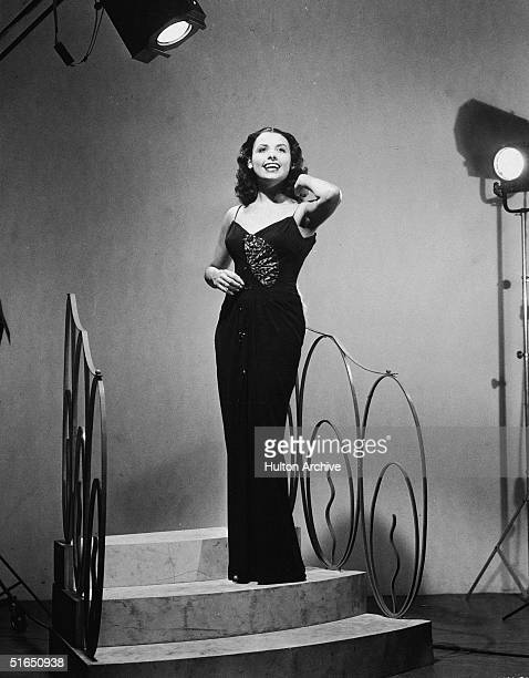 American blues singer and actress Lena Horne sings on a stage set of stairs and wears a floor length gown, 1940s.